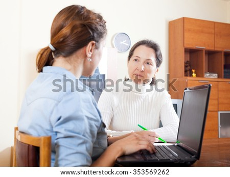 Mature woman talking with employee with laptop at home - stock photo