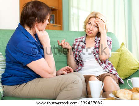 Mature woman talking with her friend and drinking tea - stock photo