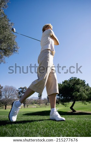 Mature woman teeing off with driver on golf course, side view (surface level)