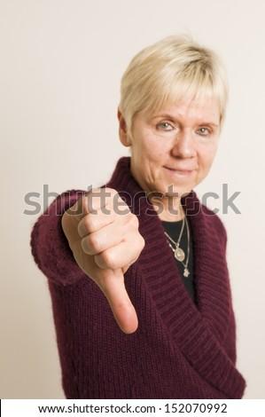 mature woman thumbs down - stock photo