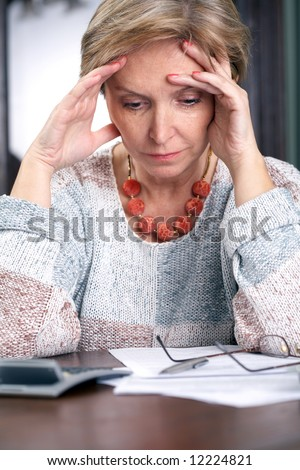 Mature woman tired of paperwork - stock photo