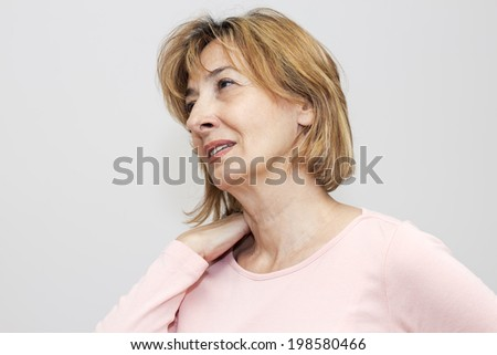 Mature woman touching her neck in pain. - stock photo