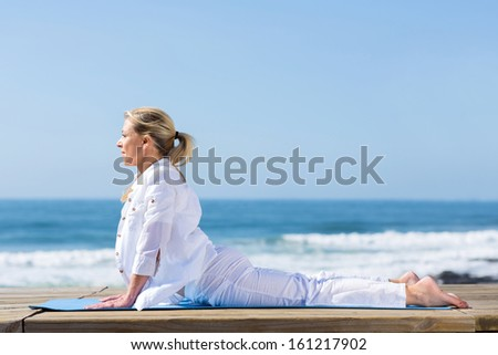 mature woman upward dog yoga position on beach - stock photo