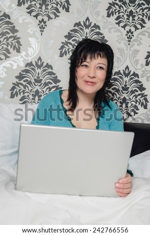 Mature woman using laptop in bed - stock photo