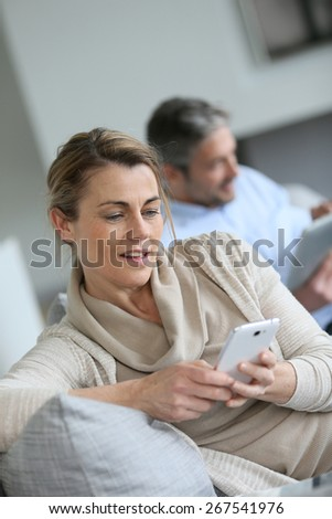Mature woman using smartphone, husband in background - stock photo