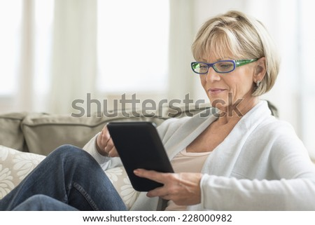 Mature woman using tablet computer while relaxing on sofa at home - stock photo