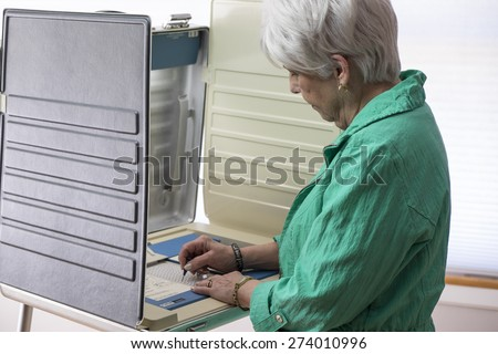 Mature woman voting at a booth, ballot casting - stock photo