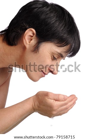 mature woman washing her face - stock photo
