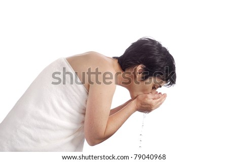 mature woman washing her face. isolated on white background - stock photo