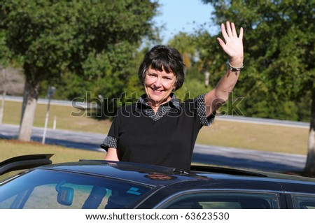 Mature woman waving through opened car sunroof