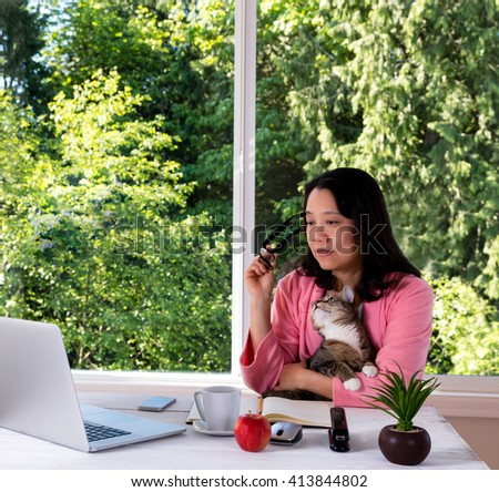 Mature woman, wearing pink bathrobe, holding her family cat while working from home in front of large window with bright daylight and trees in background.  - stock photo