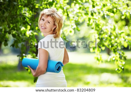 Mature woman with a gym mat outdoors - stock photo
