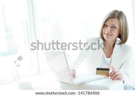 Mature woman with credit card shopping through Internet