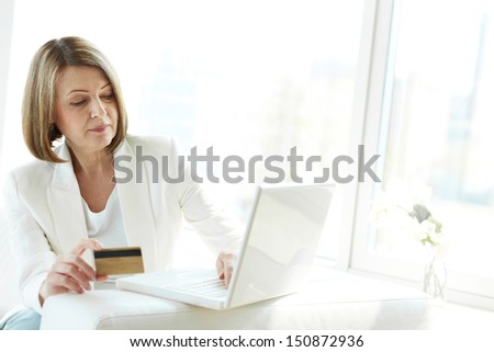 Mature woman with credit card shopping through Internet - stock photo
