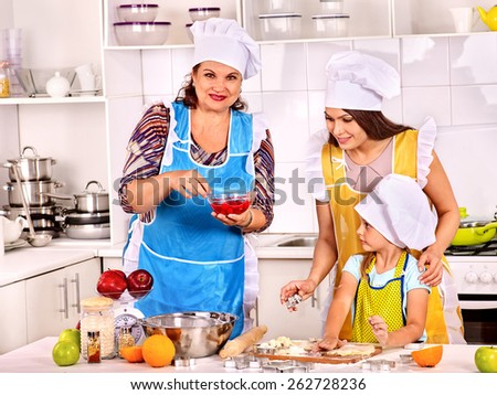 Mature woman with family preparing  dinner at kitchen. - stock photo