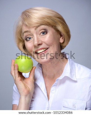 mature woman with green apple studio shot