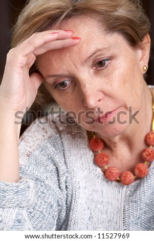 Mature woman with hand at forehead - stock photo