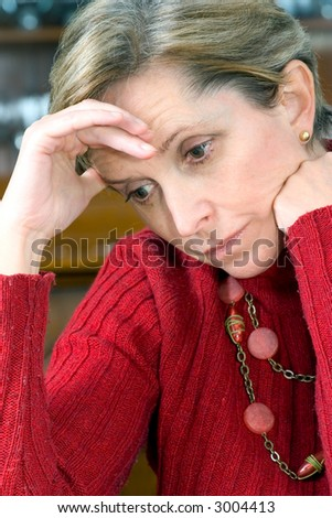 Mature woman with hand on head - stock photo
