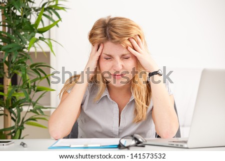 Mature woman with headache sitting at the table in the office - stock photo