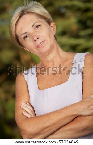 Mature woman with her arms crossed - portrait. - stock photo