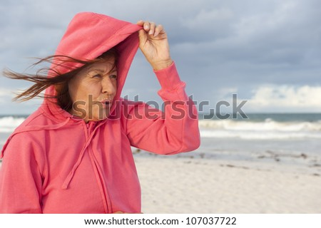 Mature woman with hooded sweater covering her head from the wind at the beach, isolated with wild ocean and storm clouds as background and copy space. - stock photo