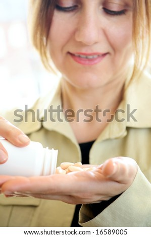 Mature woman with pills or vitamins on her hand - stock photo