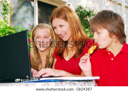 Mature woman working on computer at home with her children - stock photo