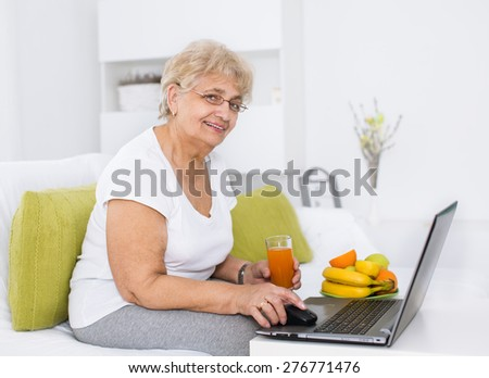 Mature woman working on laptop while holding glass of juice - stock photo