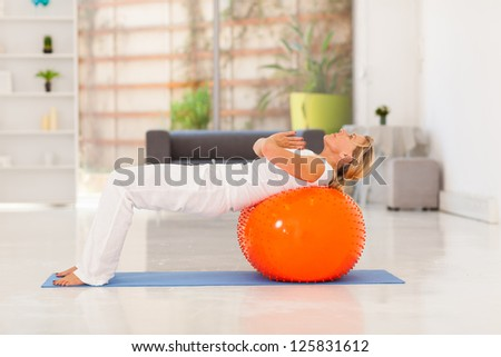 mature woman working out with exercise ball at home - stock photo