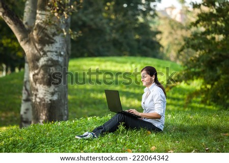 Mature woman writing on laptop sitting on the grass in the park - stock photo