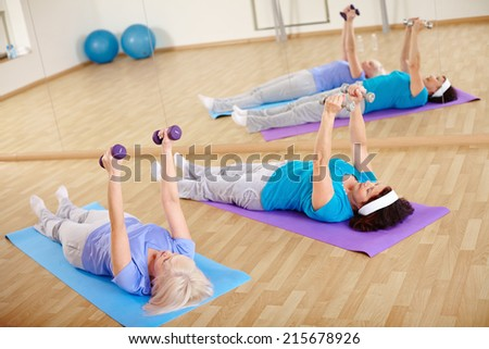 Mature women doing exercise with barbells in gym - stock photo
