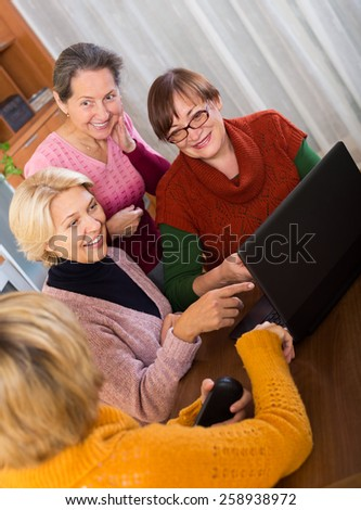 Mature women making accounts on date site in the room at home - stock photo
