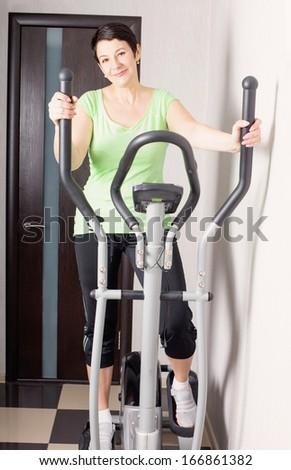 mature women on trainer machines at home - stock photo