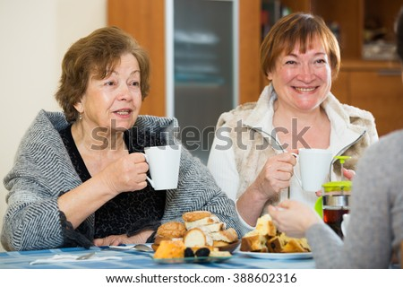 Mature women with adult girl drinking tea and chatting indoors - stock photo