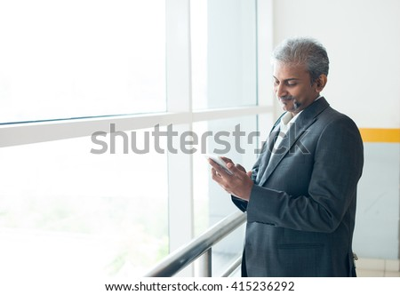 matured indian business male using  smartphone