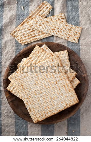 Matzah,  the unleavened bread used in the Jewish holiday passover, set on wood bowl in rustic setting - stock photo