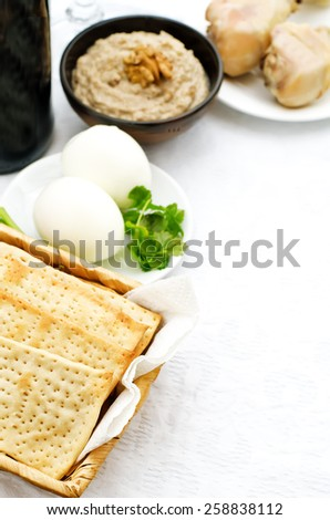Matzah, wine, eggs, chicken, greens and haroset on a white background, traditional food for the Pesach. tinting. selective focus