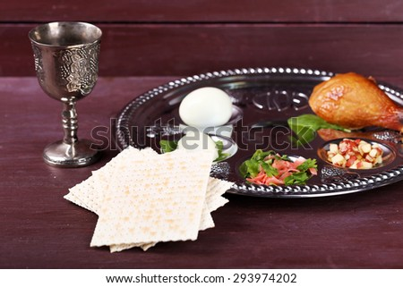 Matzo for Passover with Seder meal with wine on plate on table close up - stock photo