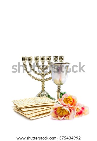 Matzo, wine, menorah and tulips for passover celebration on white background with space for text.