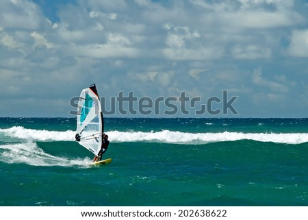 MAUI, HAWAII - SEPTEMBER 17, 2011 - Windsurfer in windy weather on September 15, 2011 in Maui, Hawaii. Windsurfing is a surface water sport that combines elements of surfing and sailing. - stock photo