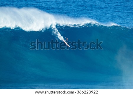 "MAUI, HI - JANUARY 16 2016: Professional surfer rides a giant wave at the legendary big wave surf break known as ""Jaws"" on one the largest swells of the year."