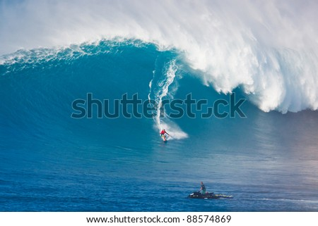 """MAUI, HI - MARCH 13: Professional surfer Yuri Soledade catches a giant wave at the legendary big wave surf break known as """"Jaws"""" during one the largest swells of the winter March 13, 2011 in Maui, HI. - stock photo"""