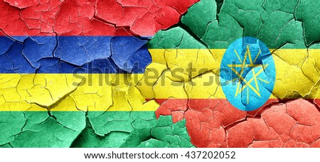 Mauritius flag with Ethiopia flag on a grunge cracked wall - stock photo