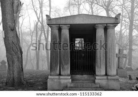 Mausoleum in a very foggy and scary looking graveyard.  Perfect for Halloween themes. - stock photo