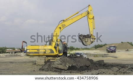 May 14, 2016 - Kuala Lumpur, Malaysia : A close-up of yellow excavator on a construction site against blue sky. - stock photo