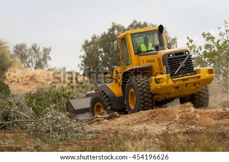 MAY 2013. NEGEV, ISRAEL. Volvo bulldozer razing the Bedouin illegal settlement.