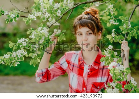 May 2016, set. Girl teenager in a red plaid shirt walking in the old courtyard, where the cherry trees bloom.