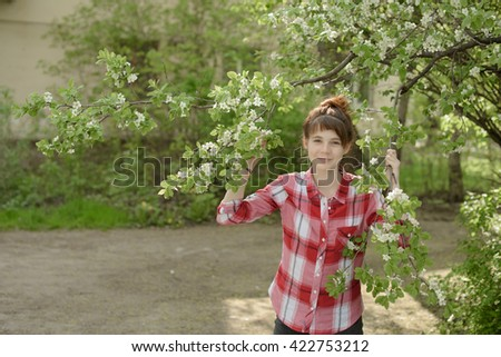 MAY 2016, the girl the teenager in a red shirt smells a branch of the blossoming cherry tree