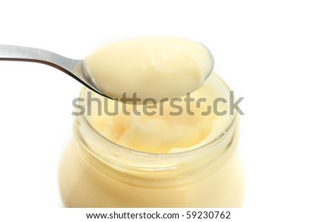 Mayonnaise on spoon isolated on white - stock photo