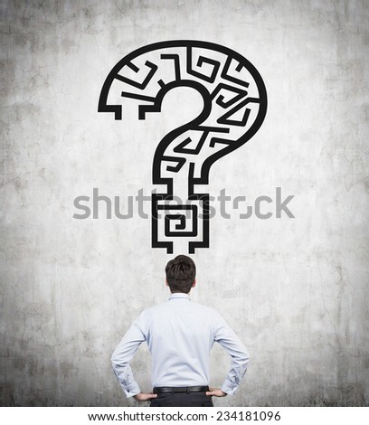 Maze in a shape of Question mark and businessman is looking for the solution.  - stock photo